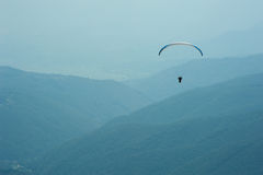 Ένα ανεμόπτερο πετά πέρα από μια κοιλάδα βουνών μια ηλιόλουστη θερινή ημέρα Στοκ φωτογραφία με δικαίωμα ελεύθερης χρήσης
