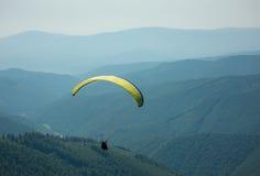 Ένα ανεμόπτερο πετά πέρα από μια κοιλάδα βουνών μια ηλιόλουστη θερινή ημέρα Στοκ Εικόνα