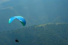 Ένα ανεμόπτερο πετά πέρα από μια κοιλάδα βουνών μια ηλιόλουστη θερινή ημέρα Στοκ φωτογραφίες με δικαίωμα ελεύθερης χρήσης