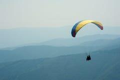 Ένα ανεμόπτερο πετά πέρα από μια κοιλάδα βουνών μια ηλιόλουστη θερινή ημέρα Στοκ Φωτογραφία