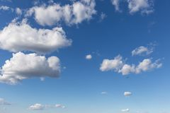 Ένα ανεμόπτερο που πετά ενάντια όμορφο σε έναν βαθύ, μπλε ουρανός, με τα μεγάλα άσπρα σύννεφα Στοκ Φωτογραφία