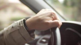 Ένα ανθρώπινο χέρι οδηγεί ένα αυτοκίνητο στο ηλιοβασίλεμα στην πόλη φω'τα μιας μεγάλης πόλης θαμπάδα υποβάθρου 4K απόθεμα βίντεο
