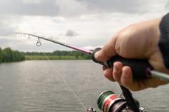 Ένα ανθρώπινο χέρι που κρατά μια περιστροφή Διαδικασία αλιείας στοκ εικόνες