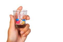 Ένα ανθρώπινο χέρι που κρατά πολλά ζωηρόχρωμα χάπια σε ένα μετρώντας φλυτζάνι του γυαλιού Στοκ Φωτογραφία