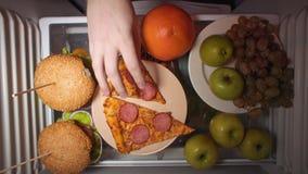 Επίπεδος βάλτε του χεριού παίρνει τα τρόφιμα τη νύχτα με στα ράφια του ψυγείου απόθεμα βίντεο