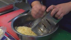 Ένα ανθρώπινο χέρι τρίβει το τυρί σε έναν ξύστη σιτηρέσιο υγιεινό κουζίνα απόθεμα βίντεο