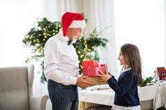 Ένα ανώτερο άτομο με ένα δόσιμο καπέλων Santa παρουσιάζει σε ένα μικρό κορίτσι στο χρόνο Χριστουγέννων στοκ εικόνες