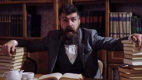 Ένα αξιοσέβαστο άτομο παρουσιάζει ποικίλες συγκινήσεις καθμένος στο γραφείο στη βιβλιοθήκη Συγκινήσεις, επιστήμη, έννοια βιβλιοθη απόθεμα βίντεο