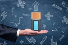 Ένα αρσενικό χέρι επιχειρηματιών ` s κρατά ψηλά μια μεγάλη πλήρως-fully-charged μπαταρία σε ένα μπλε υπόβαθρο πινάκων Στοκ Εικόνες