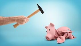 Ένα αρσενικό χέρι που κρατά ένα οικιακό σφυρί πέρα από μια σπασμένη piggy τράπεζα που βρίσκεται στα κομμάτια Στοκ Εικόνες