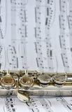 Ένα ασημένιο φλάουτο στη μουσική φύλλων στοκ εικόνα με δικαίωμα ελεύθερης χρήσης