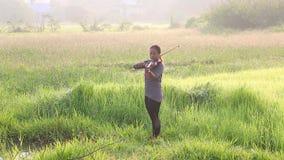 Ένα ασιατικό βιολί παιχνιδιού γυναικών στον τομέα χλόης απόθεμα βίντεο