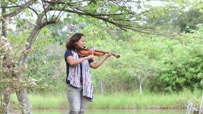 Ένα ασιατικό womanwith Jean και βιολί παιχνιδιού μαντίλι φιλμ μικρού μήκους