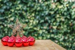 Ένα αστέρι Χριστουγέννων που περιβάλλεται από πολλές κόκκινες σφαίρες, σε έναν ξύλινο πίνακα Στοκ Φωτογραφίες