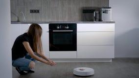 Ένα αστείο κορίτσι ταΐζει στο ρομπότ της την ηλεκτρική σκούπα με ένα σιτάρι Μια γυναίκα χαίρεται για τη νέα συσκευή ενός έξυπνου  απόθεμα βίντεο