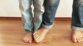 Ένα αστείο μήκος σε πόδηα της μητέρας και του γιου που περπατούν στα ο ένας του άλλου πόδια φιλμ μικρού μήκους