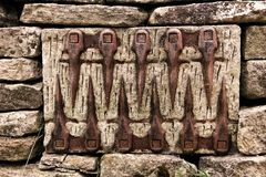 Ένα ασυνήθιστο σχέδιο του παλαιού συνόλου αγροτικών εργαλείων σε έναν τοίχο πετρών στοκ εικόνα με δικαίωμα ελεύθερης χρήσης