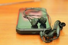 Ένα ασφαλές smartphone με τα ακουστικά σε έναν ξύλινο πίνακα Στοκ Φωτογραφίες