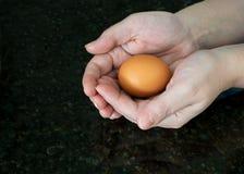 Ένα αυγό σε δύο παραδίδει το μαύρο γρανίτη στοκ εικόνα με δικαίωμα ελεύθερης χρήσης