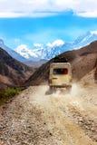 Ένα αυτοκίνητο με τους τουρίστες σε έναν δρόμο βουνών στα βουνά Himalayan στα πλαίσια των χιονωδών αιχμών Νεπάλ Το βασίλειο ο Στοκ εικόνα με δικαίωμα ελεύθερης χρήσης