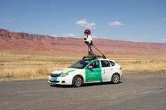 Ένα αυτοκίνητο που χαρτογραφεί έναν δρόμο στην έρημο όπως βλέπει σταθμευμένος στους vermillion απότομους βράχους στοκ φωτογραφίες