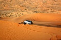 Ένα αυτοκίνητο στην άγρια χρυσή έρημο χρώματος, ανασκόπηση αμμόλοφων Στοκ εικόνα με δικαίωμα ελεύθερης χρήσης