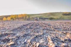 Ένα αυτοκίνητο στο αμμοχάλικο και ένας δρόμος φιαγμένος από πέτρες το καλοκαίρι στοκ εικόνα