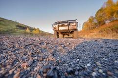 Ένα αυτοκίνητο στο αμμοχάλικο και ένας δρόμος φιαγμένος από πέτρες το καλοκαίρι στοκ εικόνες