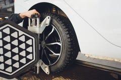 Ένα αυτοκίνητο Balancer τιμονιών αυτοκινήτων και βαθμολογεί με τον ανακλαστήρα λέιζερ συνδέεται σε κάθε ρόδα με την κεντρική οδήγ στοκ εικόνα