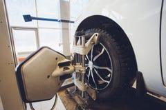 Ένα αυτοκίνητο Balancer τιμονιών αυτοκινήτων και βαθμολογεί με τον ανακλαστήρα λέιζερ συνδέεται σε κάθε ρόδα με την κεντρική οδήγ στοκ φωτογραφία
