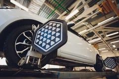 Ένα αυτοκίνητο Balancer τιμονιών αυτοκινήτων και βαθμολογεί με τον ανακλαστήρα λέιζερ συνδέεται σε κάθε ρόδα με την κεντρική οδήγ στοκ φωτογραφίες