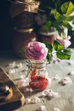 Ένα βάζο γυαλιού με εύγευστο έναν γαστρονομικό αυξήθηκε μαρμελάδα στο υπόβαθρο πετάλων και τριαντάφυλλων στο όμορφο φως στοκ εικόνες