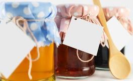 Ένα βάζο με το μέλι, η μουριά και το λουλούδι φράσσουν σε ένα άσπρο υπόβαθρο Στοκ Εικόνες