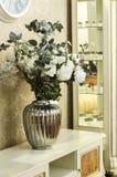 Ένα βάζο των λουλουδιών στον πίνακα με έναν καθρέφτη Στοκ Φωτογραφία