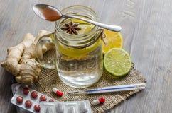 Ένα βάζο maison με το τσάι πιπεροριζών και λεμονιών με τα χάπια και θερμόμετρο στο ξύλινο υπόβαθρο Στοκ Εικόνες