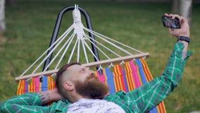 Ένα βάναυσο άτομο με μια γενειάδα βρίσκεται σε μια αιώρα στη φύση και κάνει selfie στο τηλέφωνο απόθεμα βίντεο