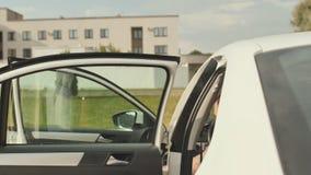 Ένα βάναυσο άτομο με τις δερματοστιξίες σε ετοιμότητα του ανοίγει την πόρτα και προκύπτει από το άσπρο αυτοκίνητό του φιλμ μικρού μήκους