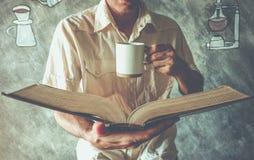 Ένα βιβλίο ανάγνωσης ατόμων με την κατανάλωση του καφέ ή του τσαγιού Στοκ Εικόνα