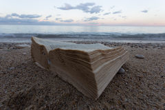Ένα βιβλίο και σε μια εγκαταλειμμένη παραλία στο υπόβαθρο μια παραλία Στοκ Εικόνες