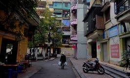 Ένα βιετναμέζικο πρόσωπο περπατά σε μια ζωηρόχρωμη οδό του Ανόι Στοκ φωτογραφία με δικαίωμα ελεύθερης χρήσης