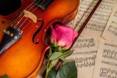 Ένα βιολί, κόκκινο αυξήθηκαν και η μουσική φύλλων Στοκ φωτογραφία με δικαίωμα ελεύθερης χρήσης
