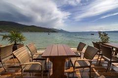 Ένα βλέμμα μέσω των υγρών πινάκων και των καρεκλών Ο ζαλίζοντας ουρανός επάνω από τη λίμνη της Οχρίδας μετά από τη βροχή Ενάντια  στοκ φωτογραφία με δικαίωμα ελεύθερης χρήσης