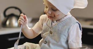 Ένα βρώμικο αγόρι σε μια μαγειρική ΚΑΠ τρώει τη σοκολάτα με ένα δίκρανο στην κουζίνα απόθεμα βίντεο
