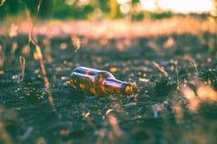 Ένα βρώμικο κενό μπουκάλι μπύρας βρίσκεται στο έδαφος Στοκ Εικόνες