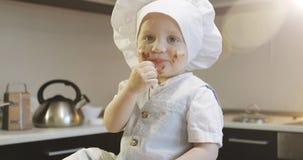 Ένα βρώμικο παιδί σε μια μαγειρική ΚΑΠ τρώει τη σοκολάτα στην κουζίνα απόθεμα βίντεο