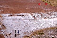 Ένα γήπεδο ποδοσφαίρου με τα παιδιά που παίζουν το ποδόσφαιρο μετά από τη βροχή στα βουνά ατλάντων στο Μαρόκο Στοκ φωτογραφία με δικαίωμα ελεύθερης χρήσης