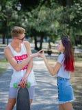 Ένα γελώντας κορίτσι με τη μακριά τρίχα κάστανων που χρονολογεί με έναν ελκυστικό συνεργάτη σε ένα πάρκο σε ένα φυσικό θολωμένο υ στοκ φωτογραφίες
