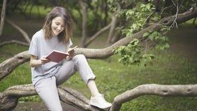 Ένα γελώντας λευκό κορίτσι brunette διαβάζει ένα βιβλίο στο πάρκο Στοκ Εικόνες