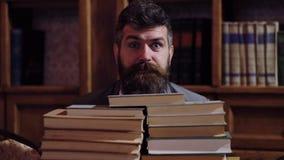 Ένα γενειοφόρο άτομο κοιτάζει μέσω μιας δέσμης των βιβλίων και παρουσιάζει ποικίλες συγκινήσεις Έννοια της εκδήλωσης των συγκινήσ απόθεμα βίντεο