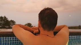Ένα γενειοφόρο άτομο κολυμπά σε μια υπαίθρια λίμνη στο ηλιοβασίλεμα σε θερινές διακοπές βίντεο που λαμβάνεται στο κινητό τηλέφωνο απόθεμα βίντεο
